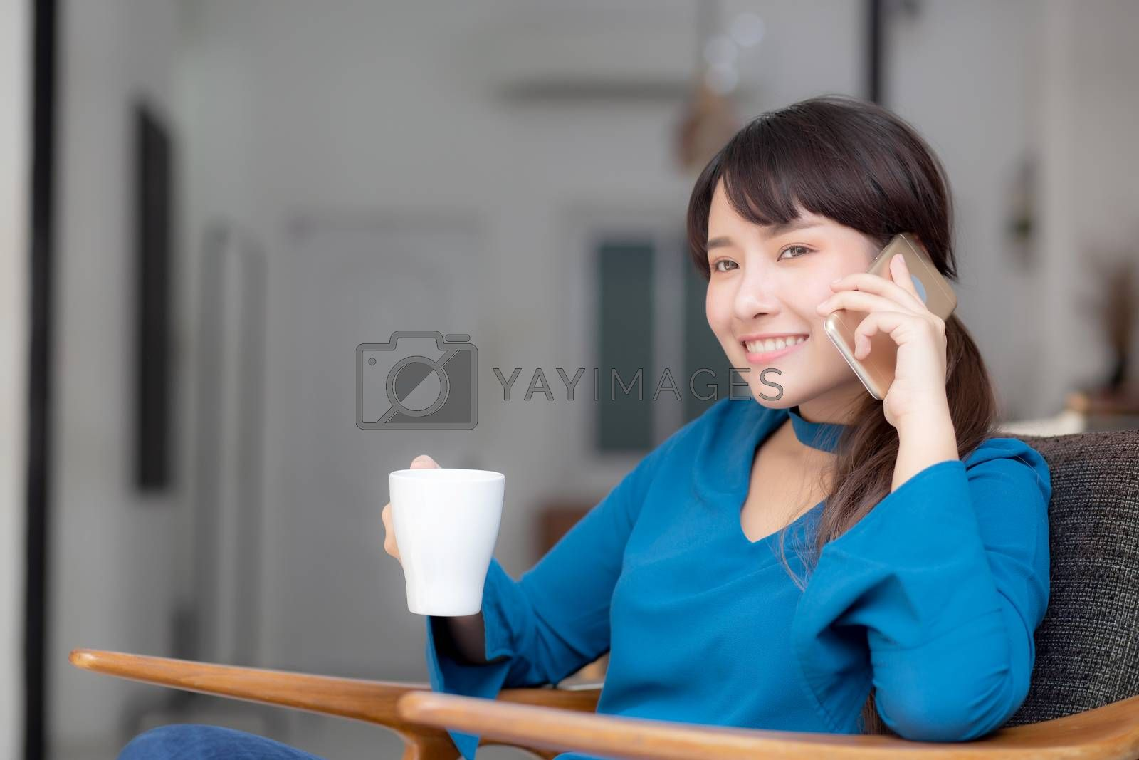 Beautiful portrait young asian woman smiling using mobile smart phone talking enjoy and drink coffee with relax, girl sitting on chair at living room, communication concept.