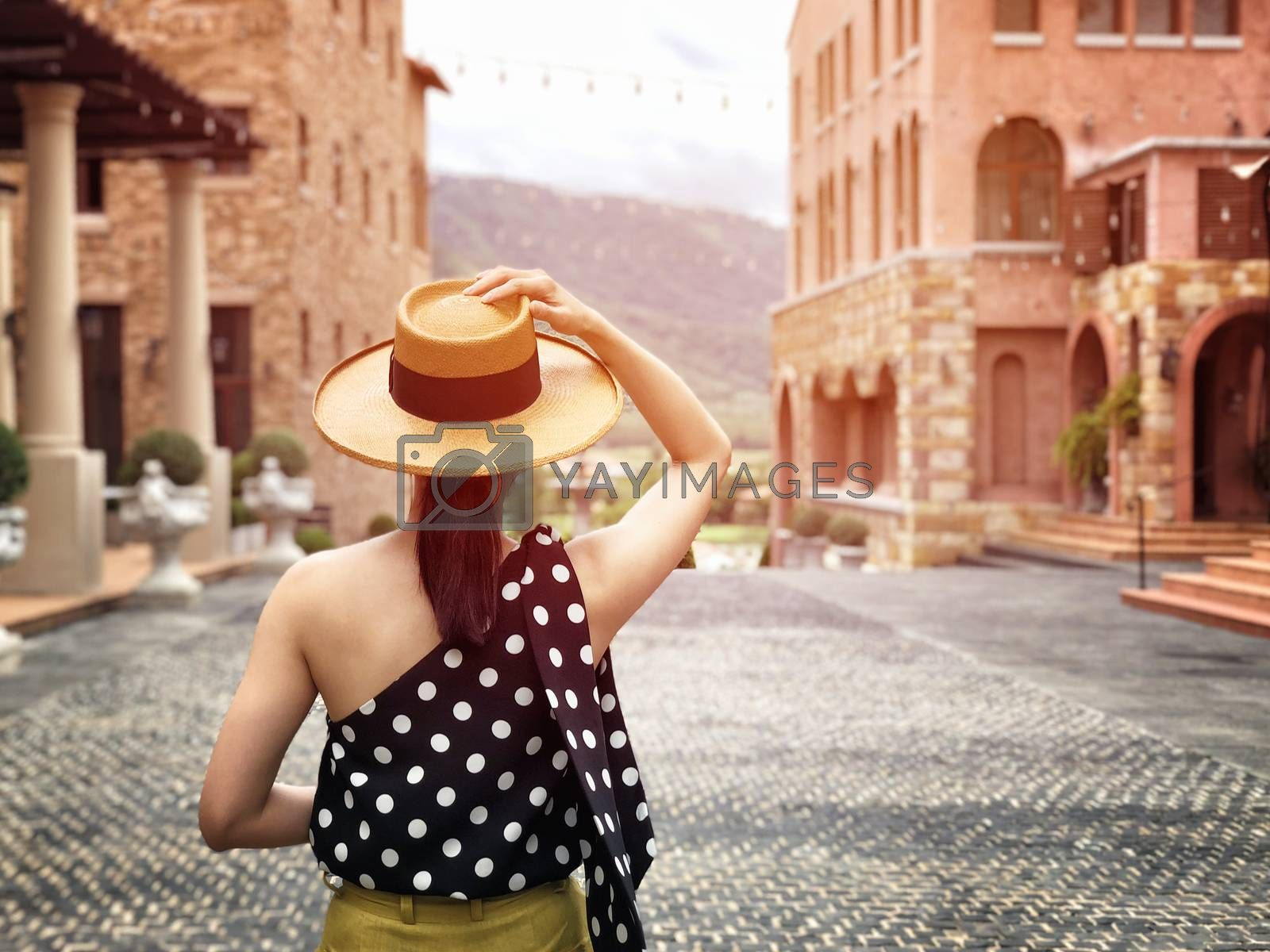 Woman wearing a planter panama hat visiting an Italian style village in summer