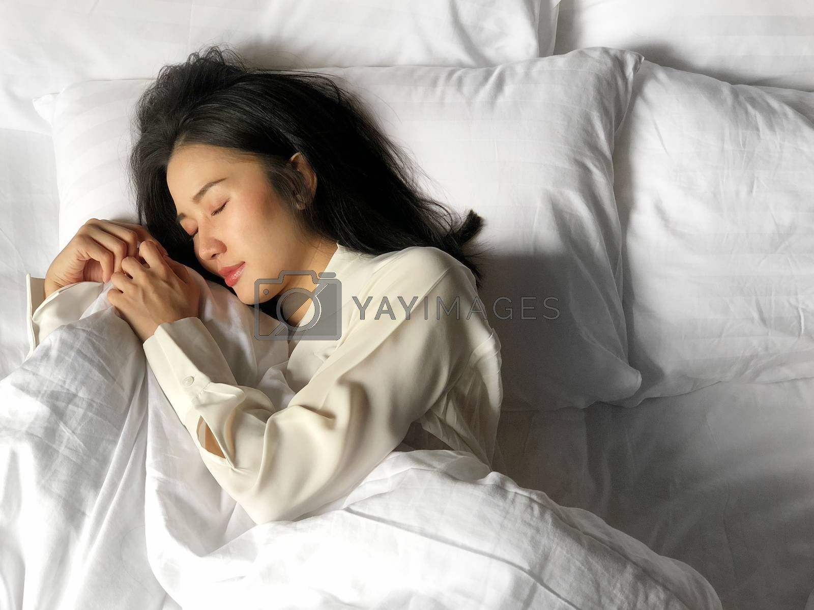Beautiful asian woman sleeping in bed under white quilt with head on pillow comfortable and happy. girl with relax for health concept.