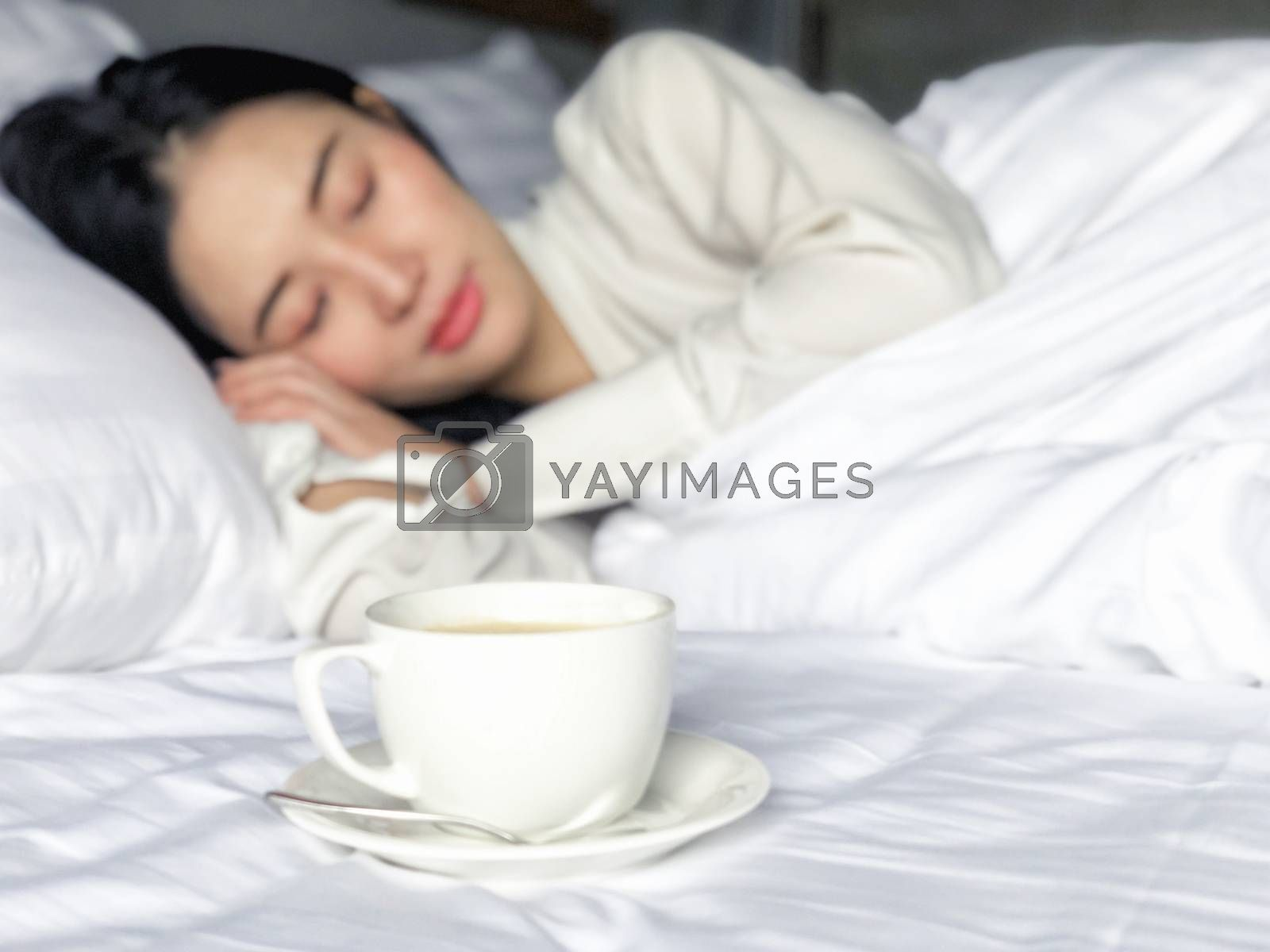 Beautiful Asian woman sleeping with a morning cup of coffee in bed