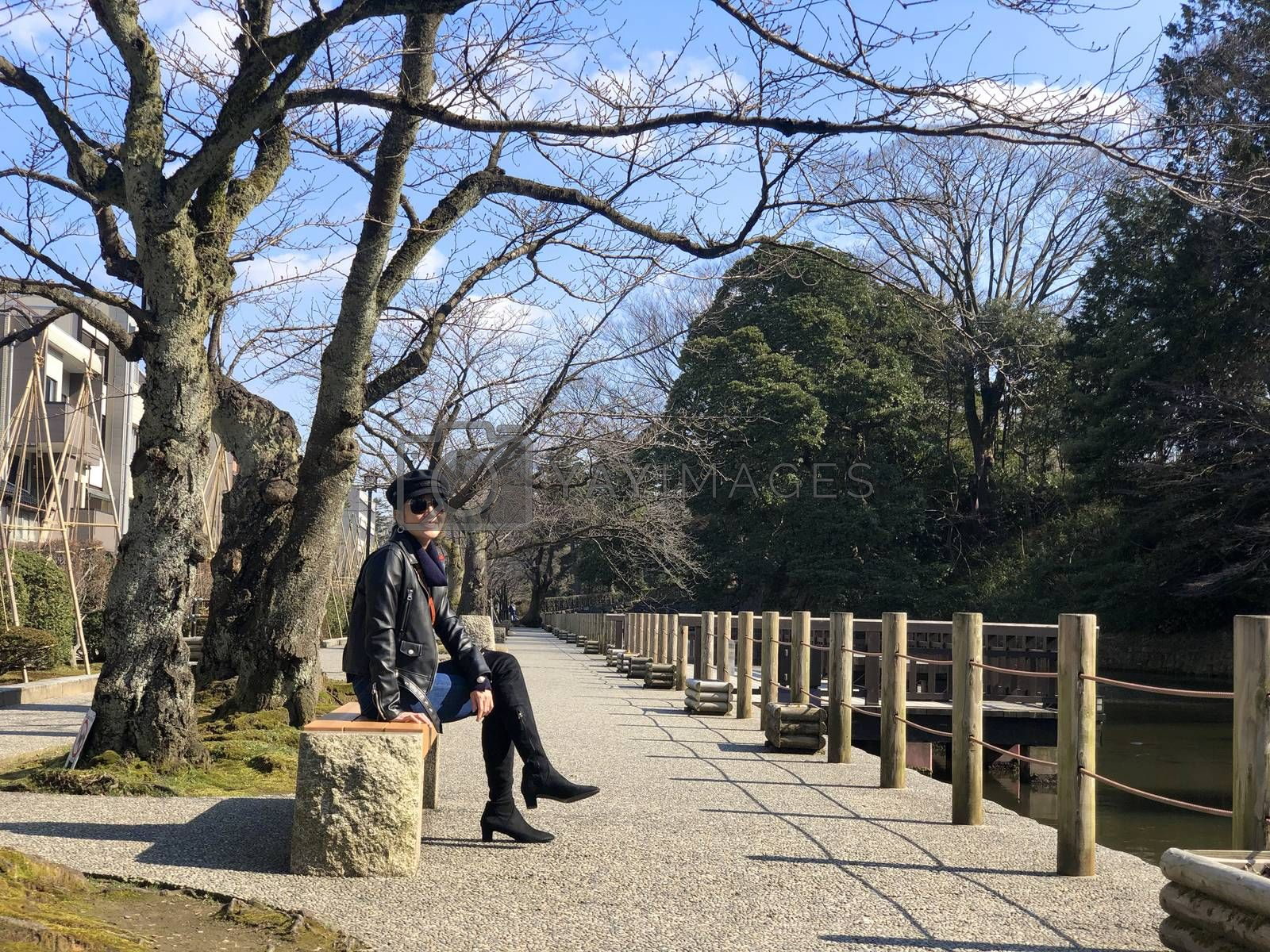 Woman sitting and seeing view around Kenrokuen garden and Kanazawa castle on her relax time.