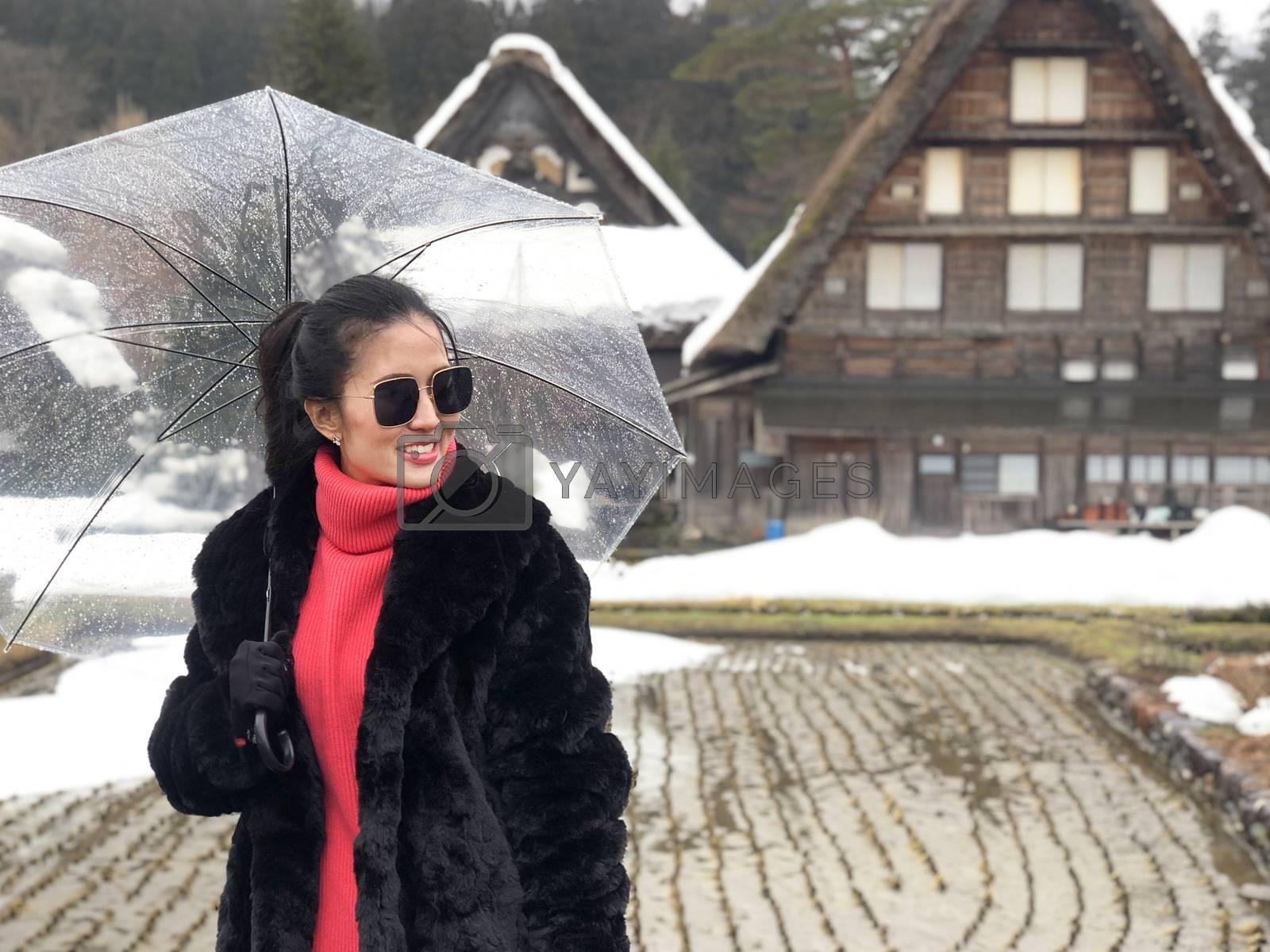 Woman tourist holding transparent umbrella in the winter and snow is falling at Shirakawago village at Gifu, Japan.