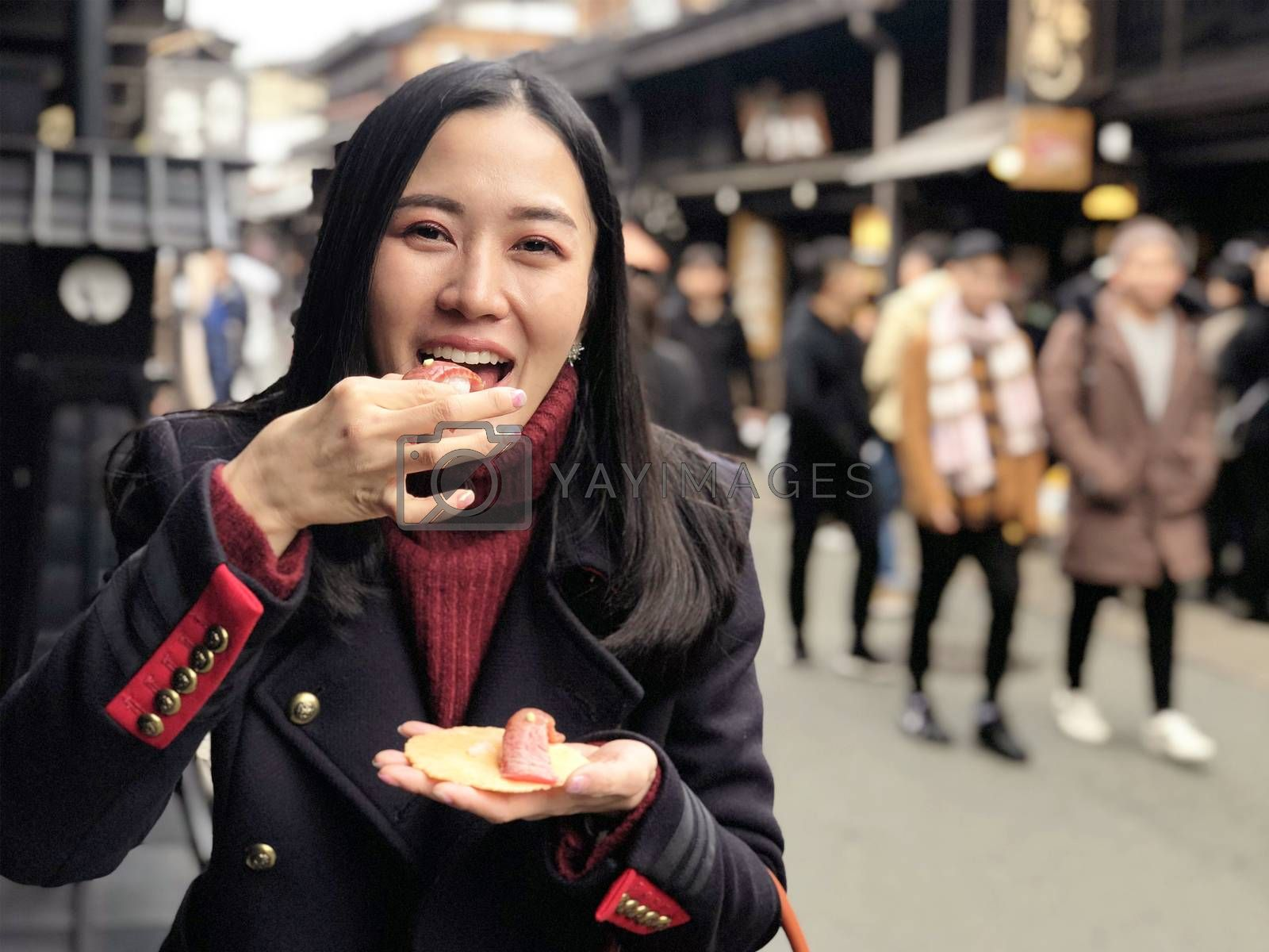 Young woman tourist enjoy eating Japanese street food Hida Beef Sushi and cracker at Takayama, Japan