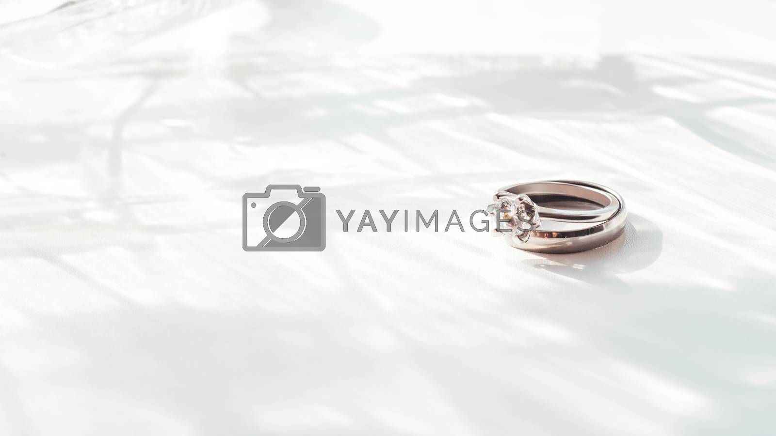 Wedding and engagement rings with diamond. Symbol of love and marriage on white background with laced shadow. Sunlight on white background.