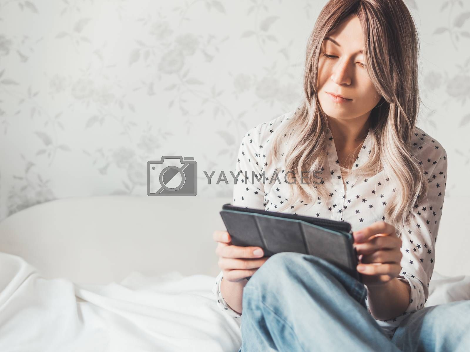 Woman sits on bed with tablet PC. She watches online TV series. Online video call or conference, distance learning, remote education. Self isolation during quarantine.