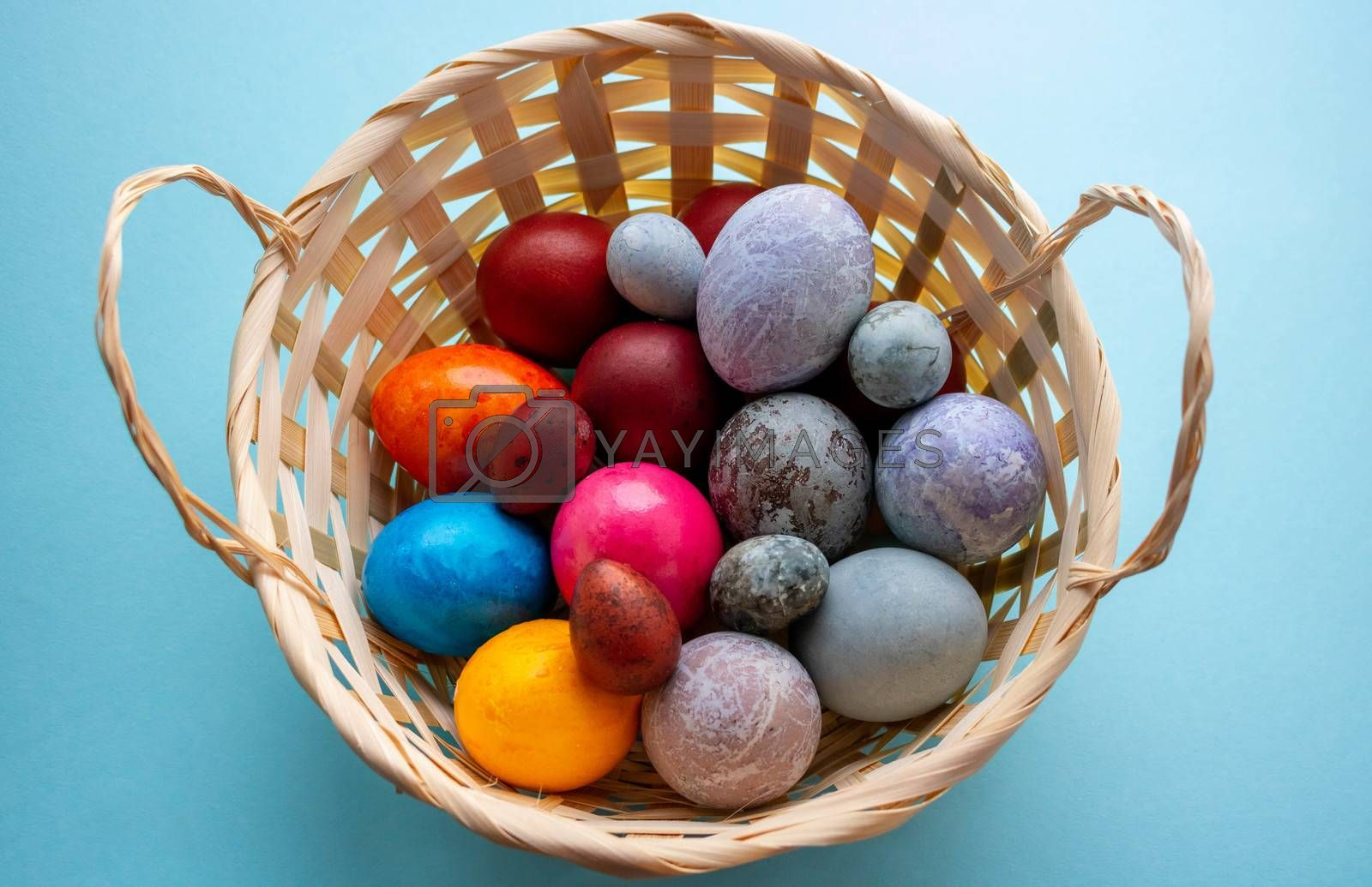 On a blue background, a basket with colorful Easter eggs.The Concept Of Easter.