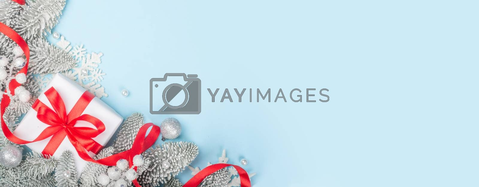 Frosted fir tree twigs and Christmas decorative gift with red ribbon on blue background with copy space for text template flat lay top view design