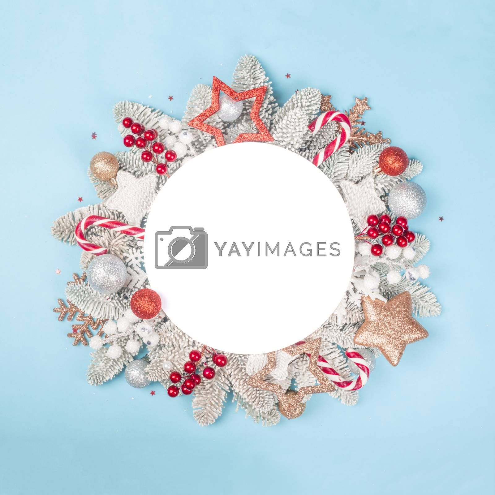 Frosted fir tree twigs and Christmas decorative bauble balls on blue background with white circle card with copy space for text template flat lay top view design