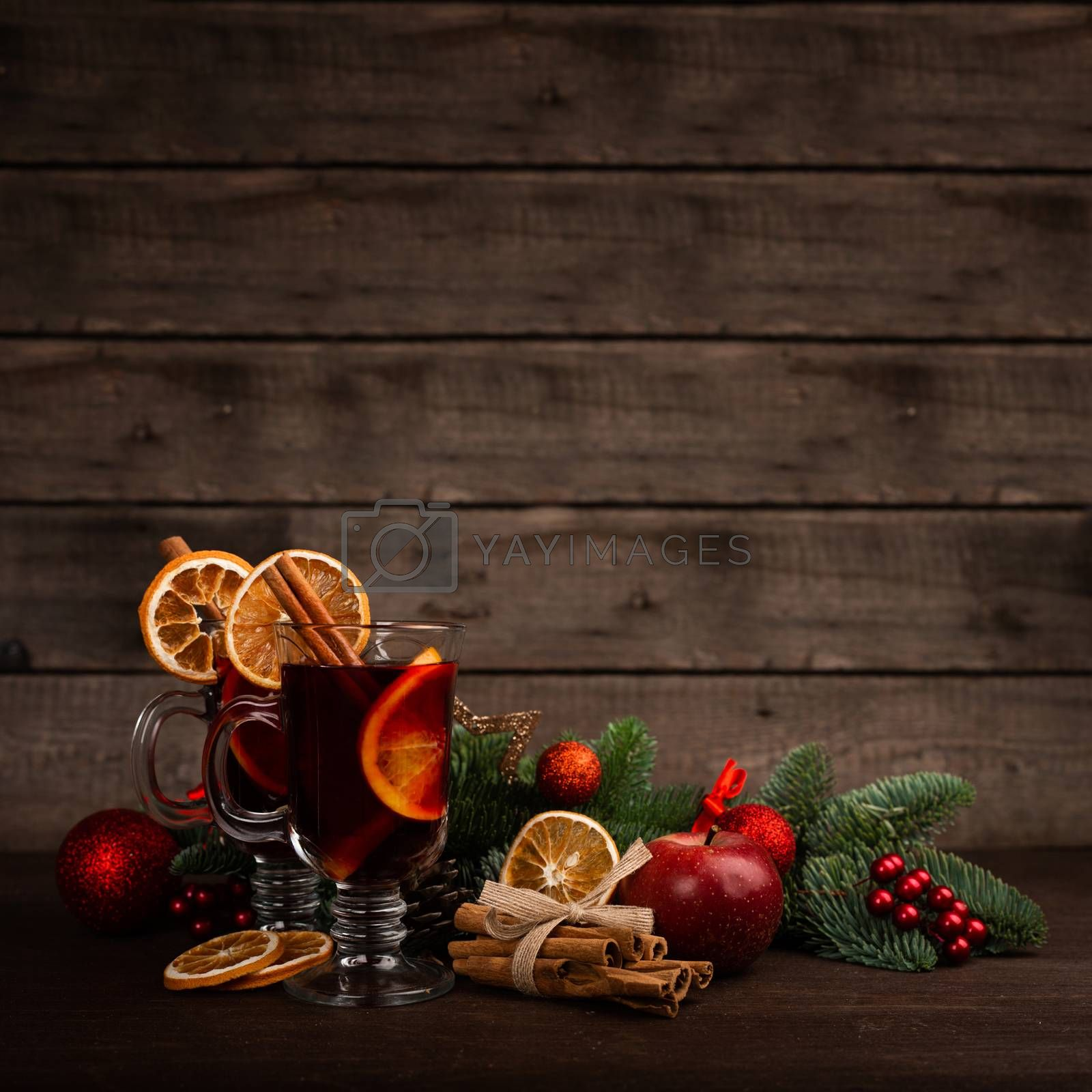 Mulled wine with cinnamon sticks orange fir tree branch and baubles Christmas composition over dark wooden background
