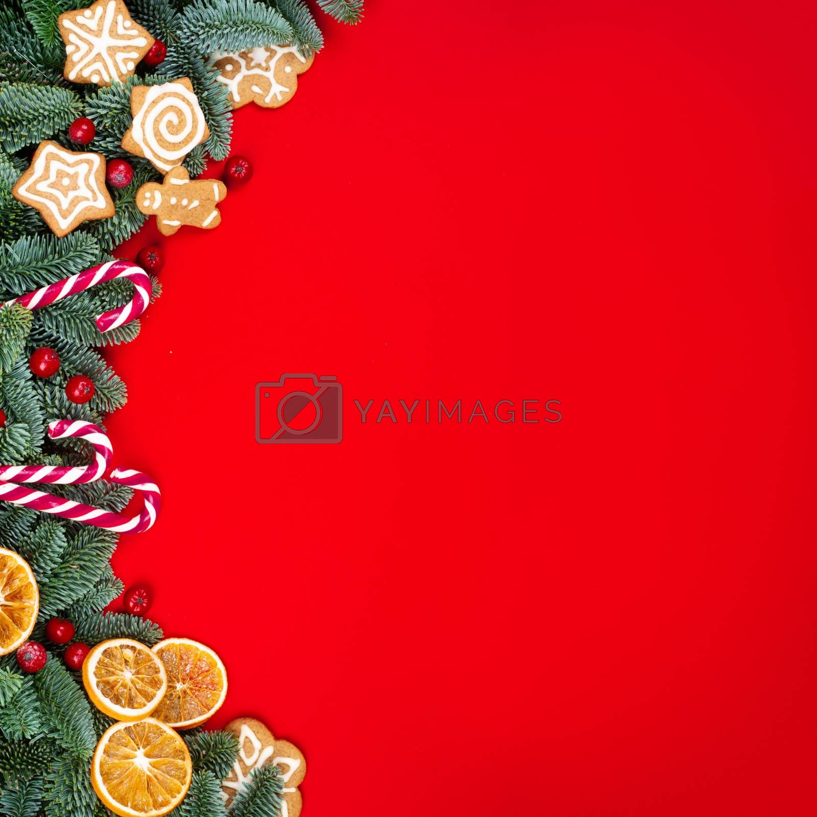 Christmas fir tree branches and decor border frame on red background with copy space for text