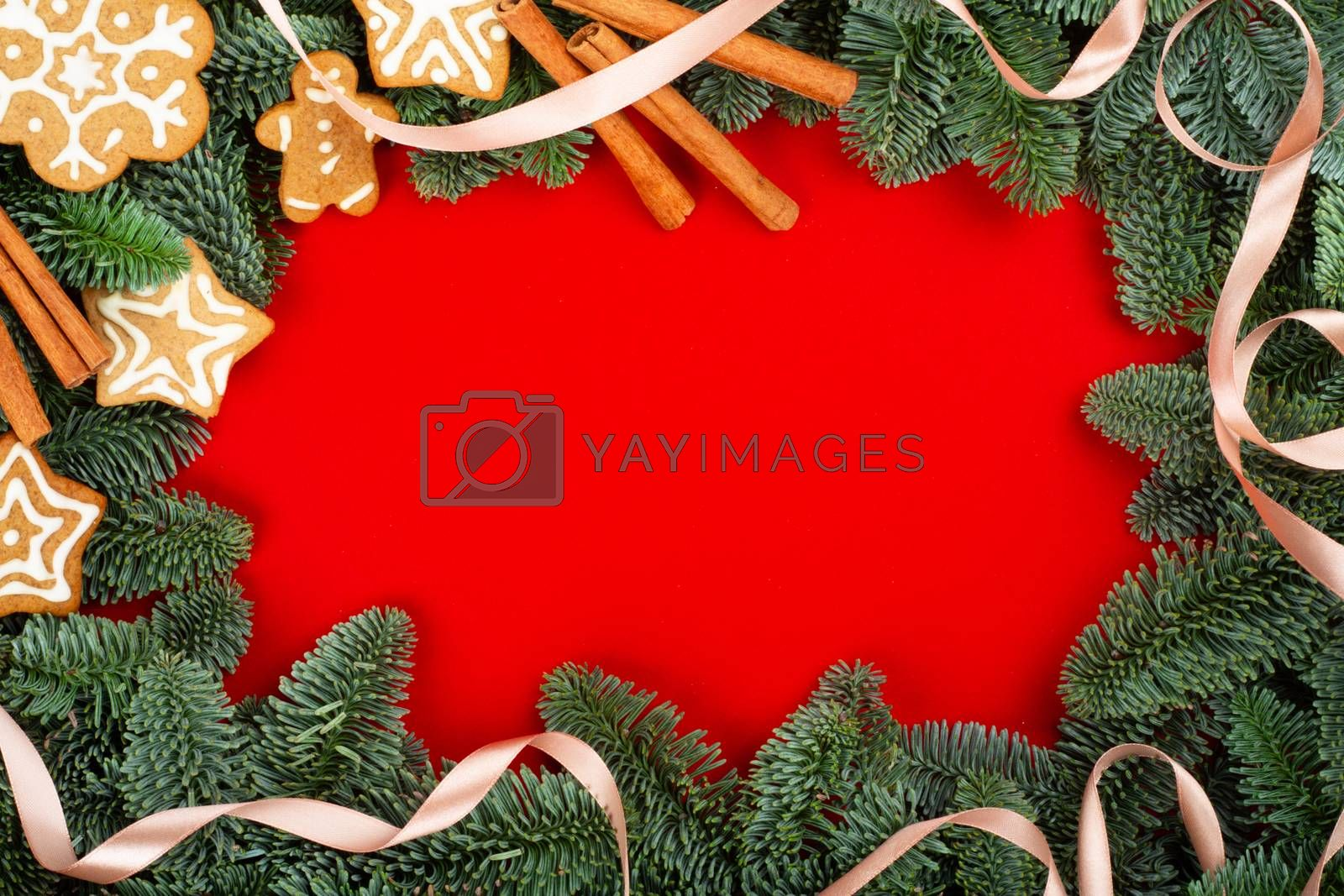 Christmas fir tree branches and food decor border frame on red background with copy space for text