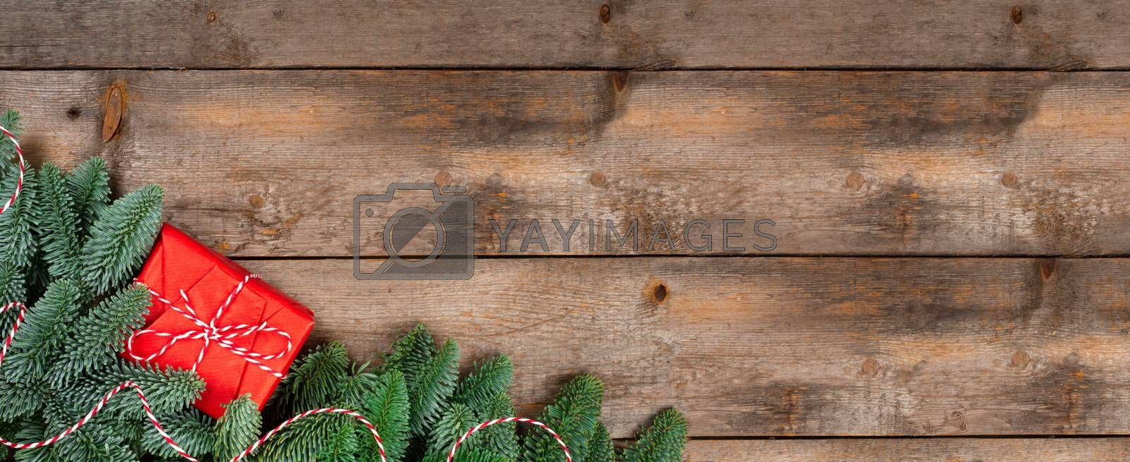 Christmas noble fir tree twigs and gift with red striped ribbon on wooden background with copy space for text