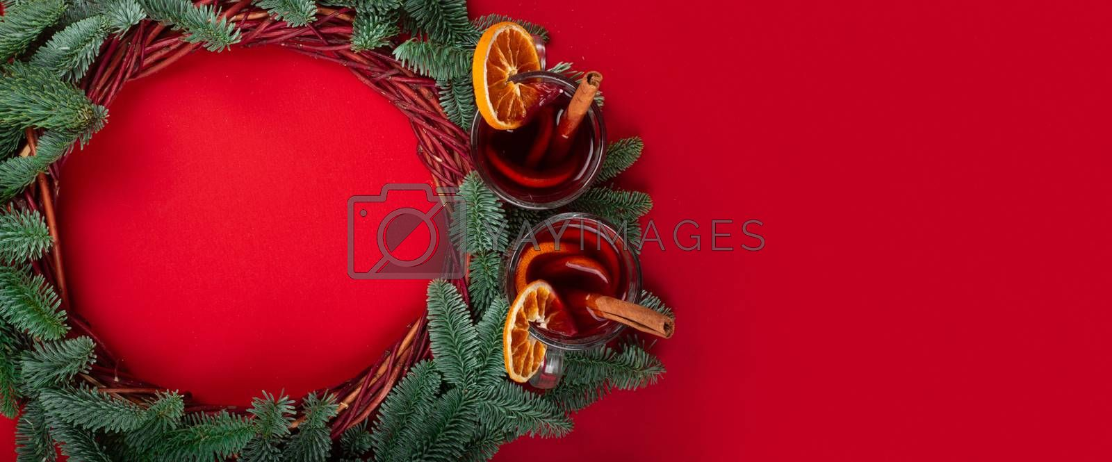 Christmas decorative wreath with noble fir tree twigs and mulled wine on red paper background with copy space for text