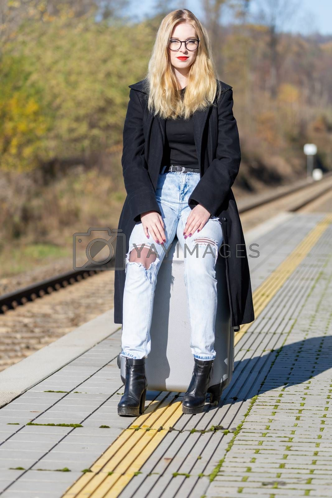 Young woman is sitting on suitcase in the railway station looking at the camera in the sunny autumn day
