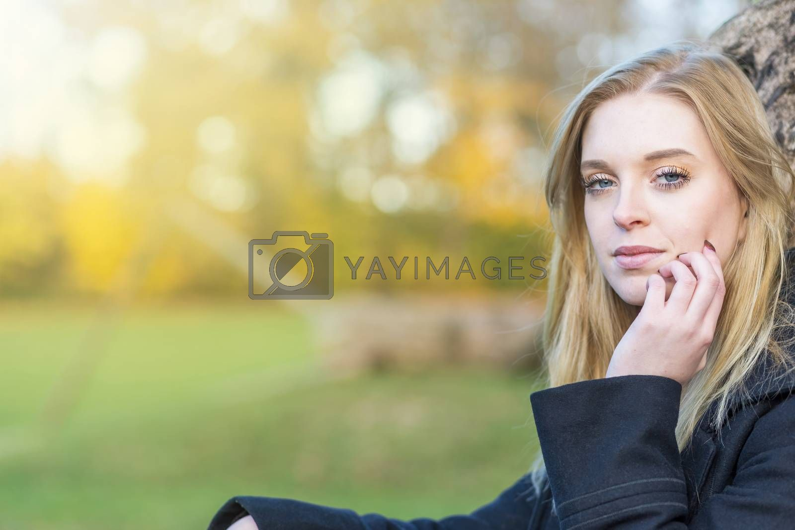 Cool young woman is posing in the autumn park looking at the camera. Horizontally.
