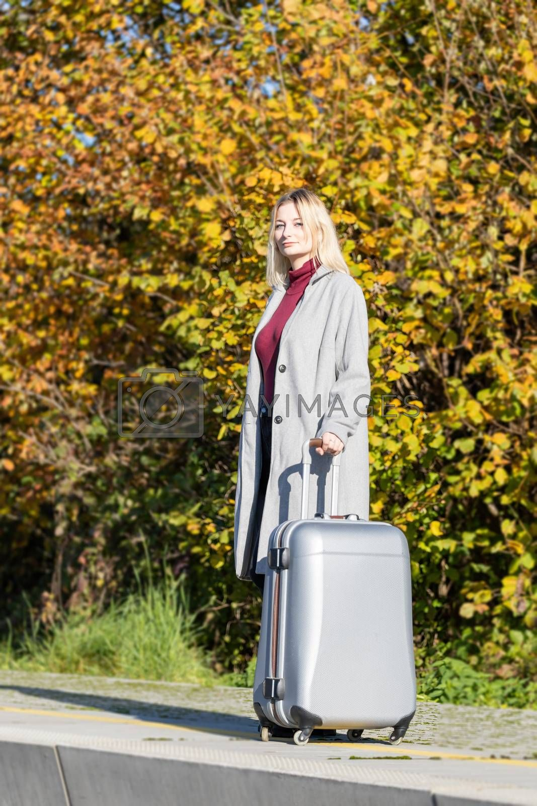 Young blond girl is posing with suitcase in the railway station looking at the camera in the sunny autumn day.