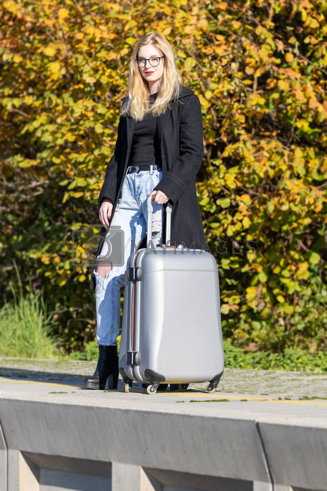 Young woman is posing with suitcase in the railway station looking at the camera.
