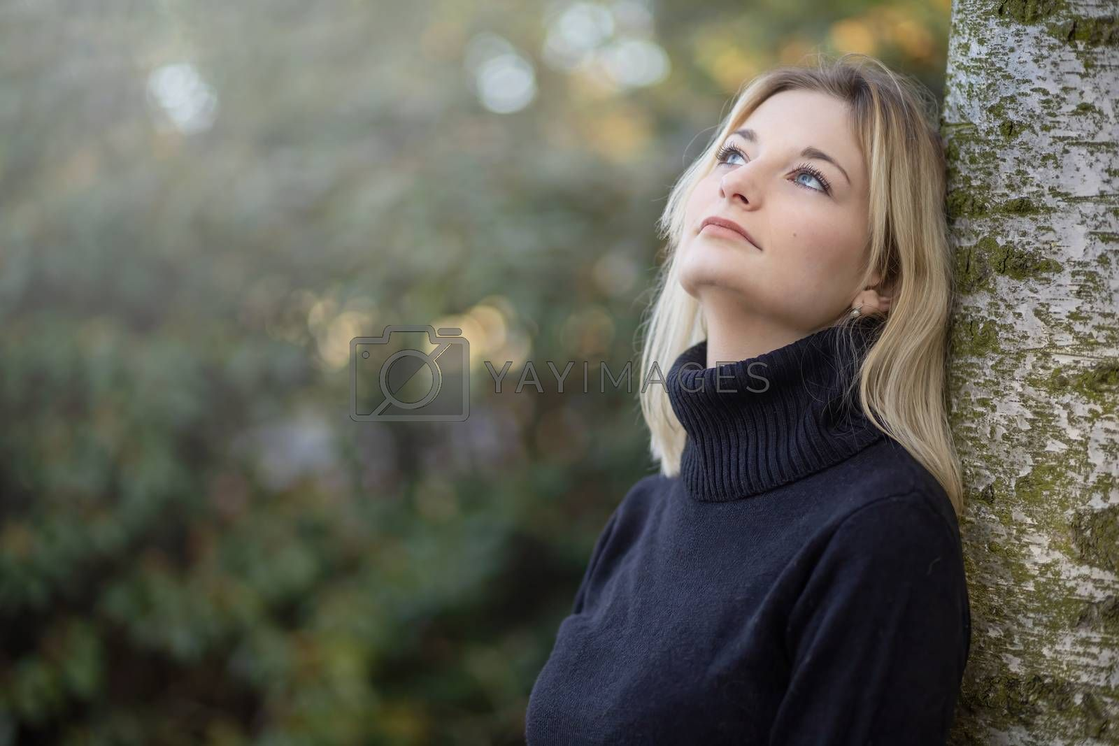 Serious young girl dressed in  turtleneck is posing in the autumn park looking up. Horizontally.