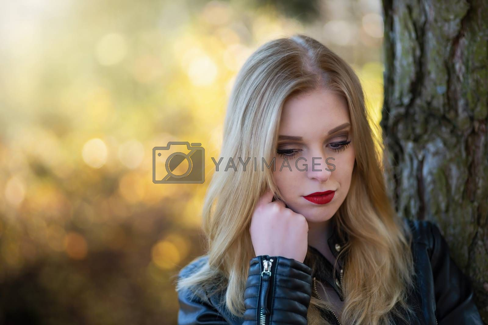 Portrait of attractive serious young woman with red lips posing in the autumn park. Horizontally.