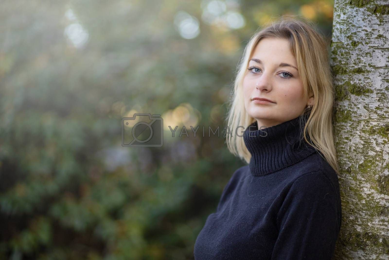 Cool young girl dressed in turtleneck is posing in the autumn park looking at the camera. Horizontally.