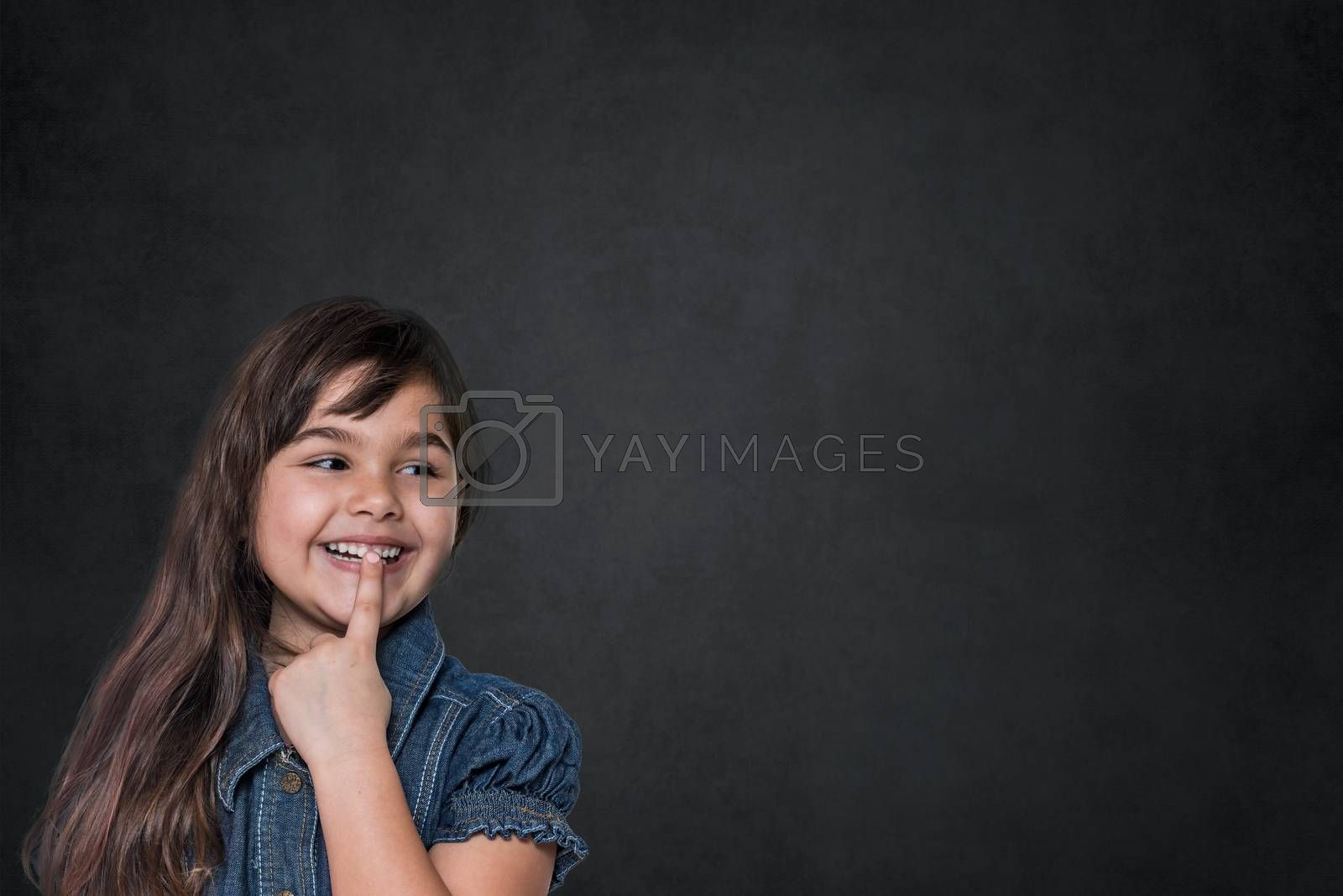 Smiling tanned long haired little girl is looking at  blank black chalkboard ready for your text.