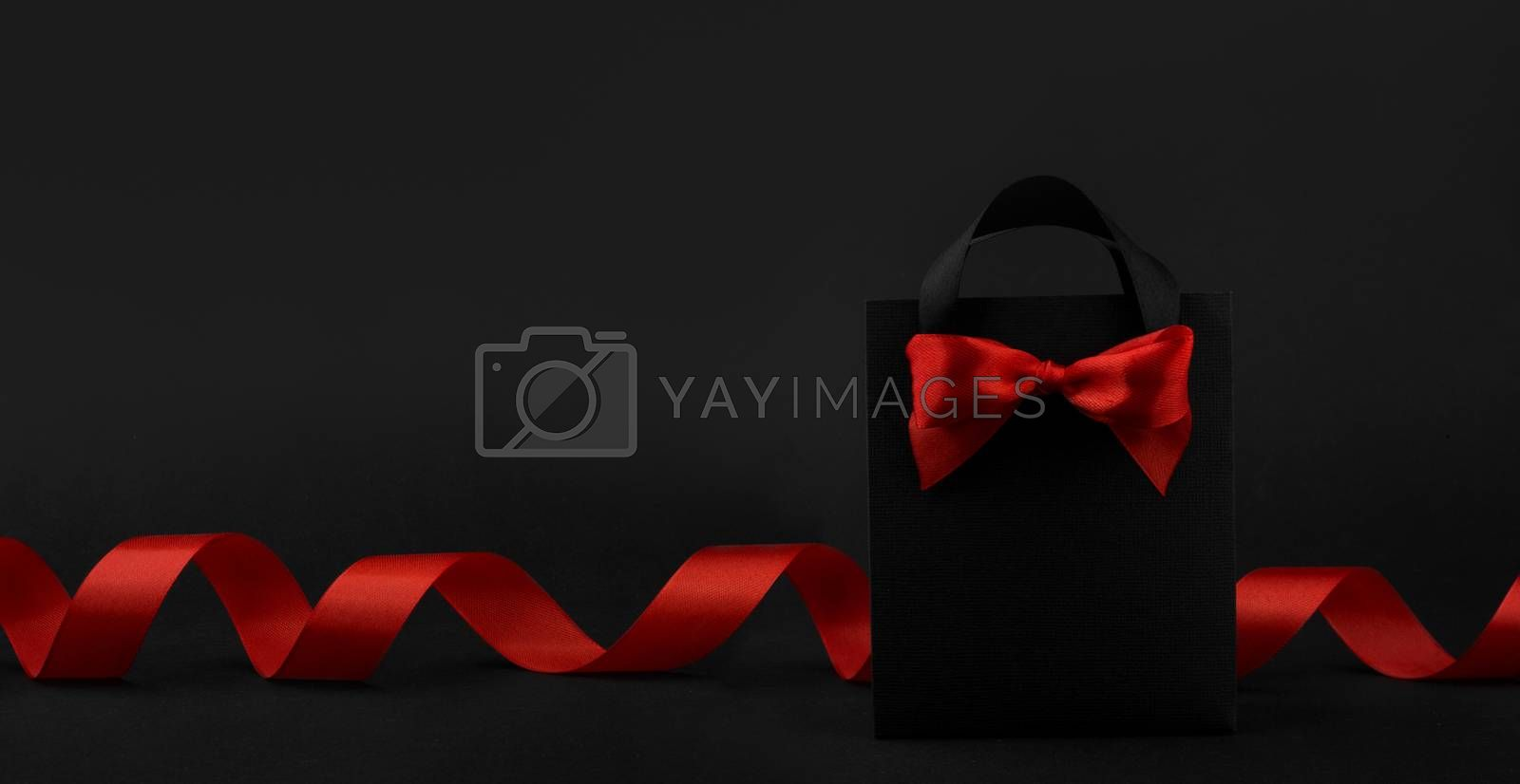Gift in black paper bag with red ribbon on black background, design banner black friday sale concept copy space for text