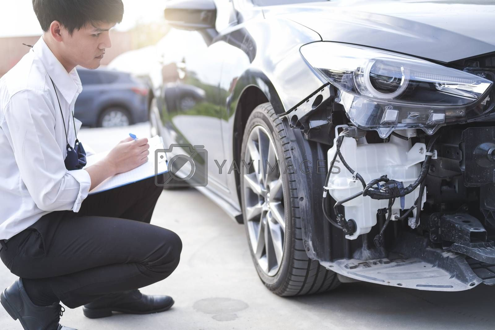 Asian saleman inspector checking writing on clipboard change wheels in garage of dealership mechanic In showroom car and insurance for check to travel to happy new year 2021