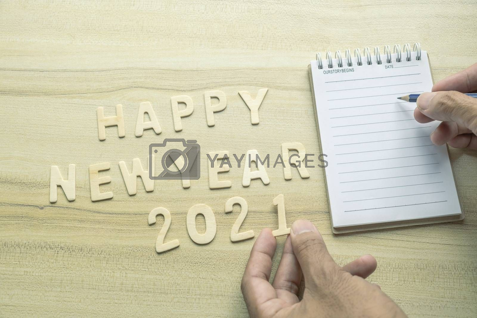 notepad with pencil, gift  and number 2021 on wood backgorund for happy new year 2021 image.For welcome new year photo.