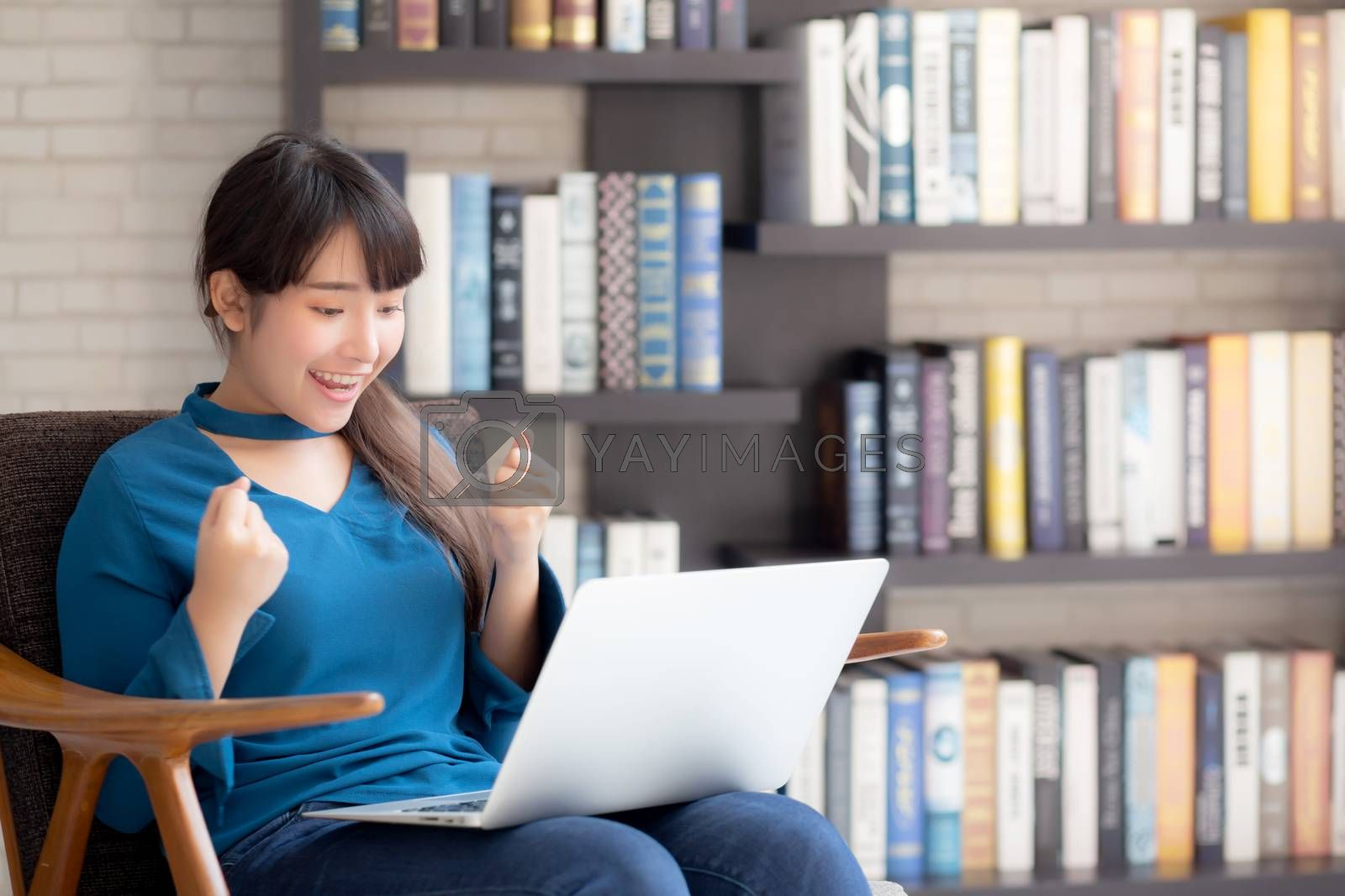 Beautiful of portrait happy young freelance asian woman using laptop work with success on chair in the home, asia girl and notebook shopping online with glad, communication concept.