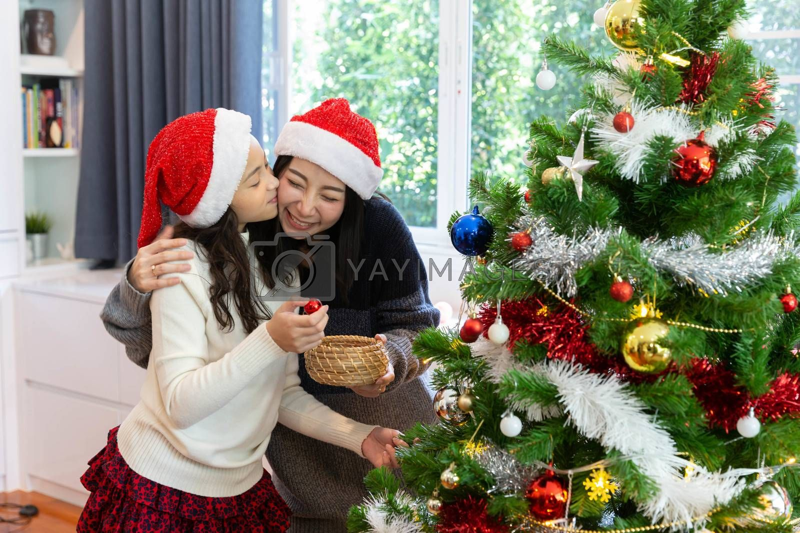 Daughter kiss her mom while decorate the christmas tree during the christmas holiday