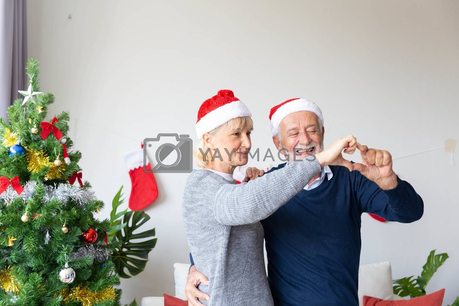 Senior retirement couple happy dancing and make a heart with their hands in living which decorated by Christmas tree during the Christmas time