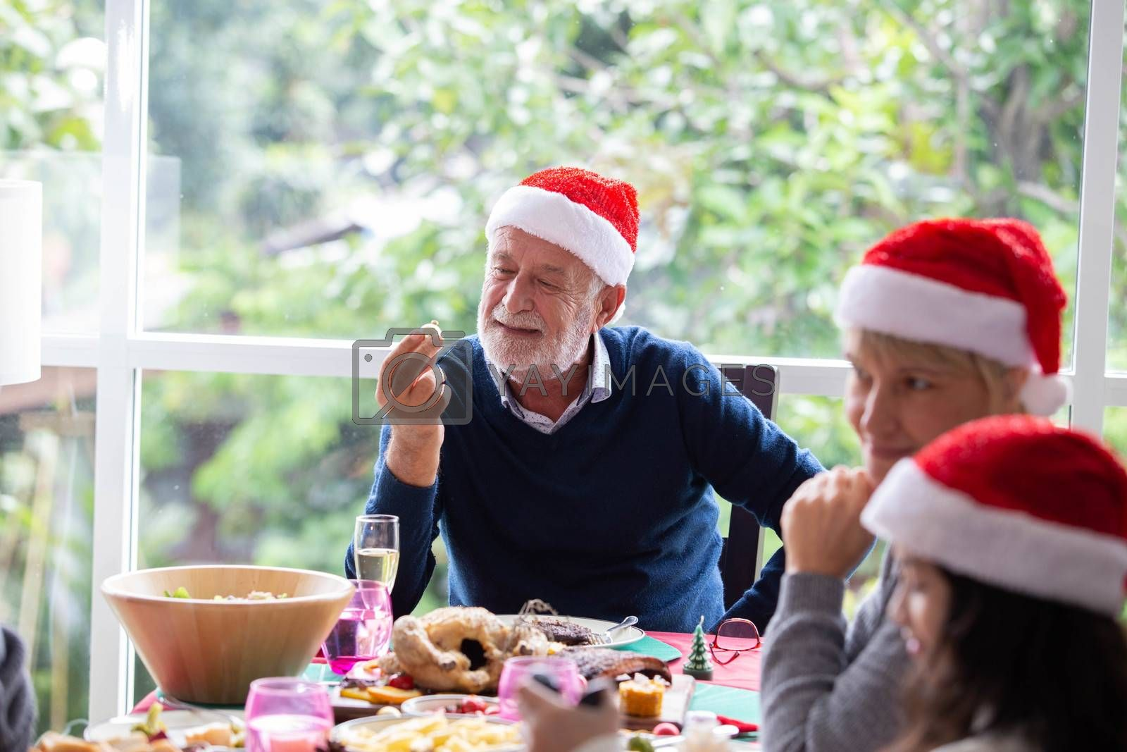 Senior retirement male is happy while having a meal with his family during christmas holiday