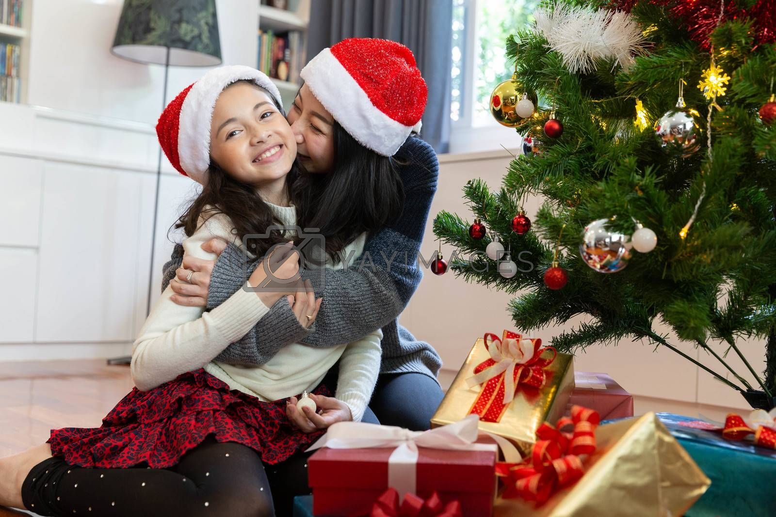 Mom kiss her daughter while decorate the christmas tree during the christmas holiday