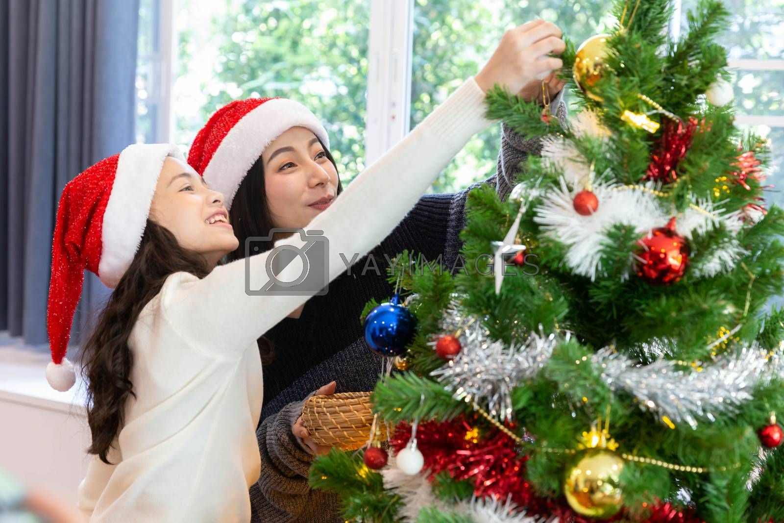Mom and her daughter decorate the christmas tree during the christmas holiday