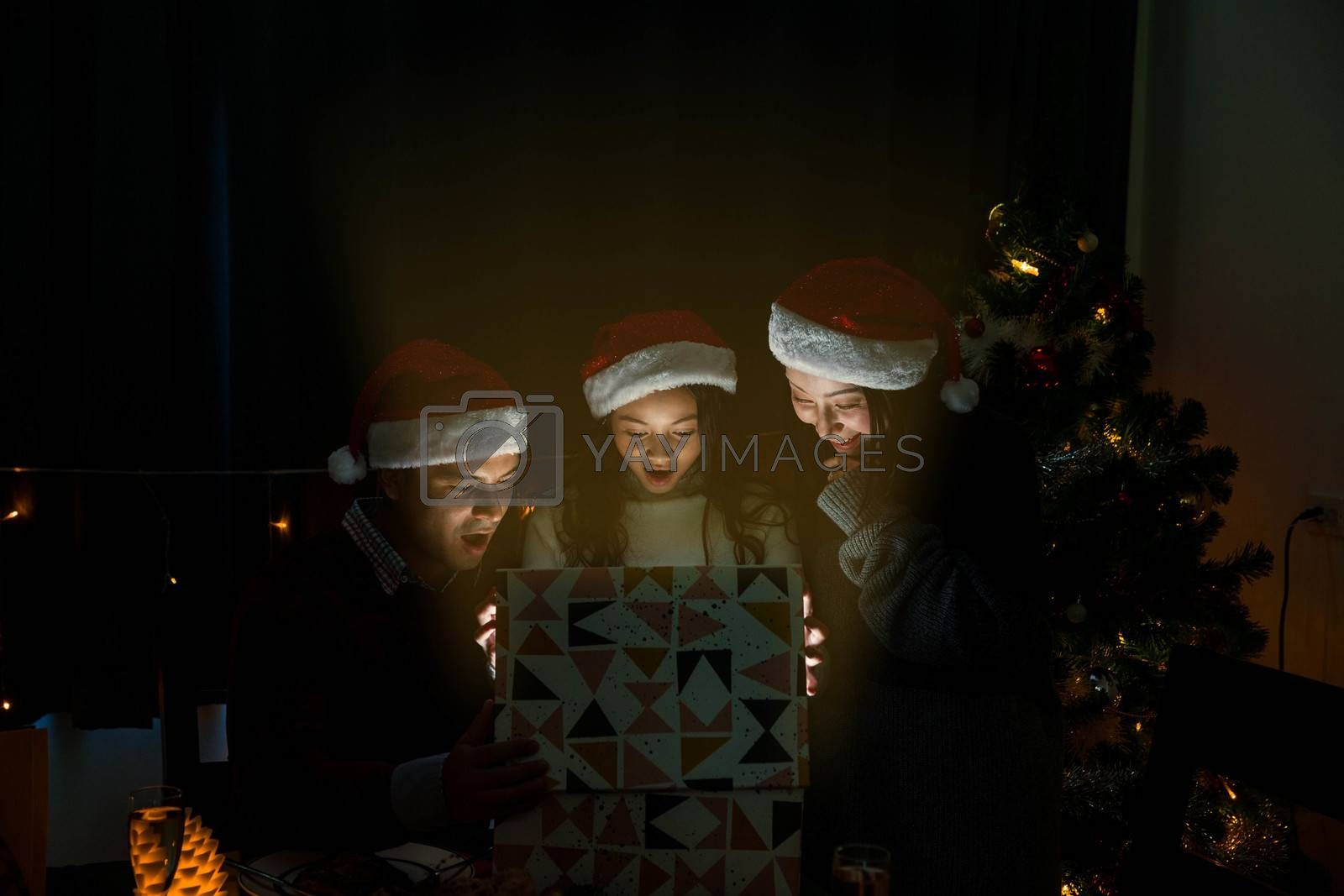 happy family open the Christmas present together and surprise their daughter during the dinner