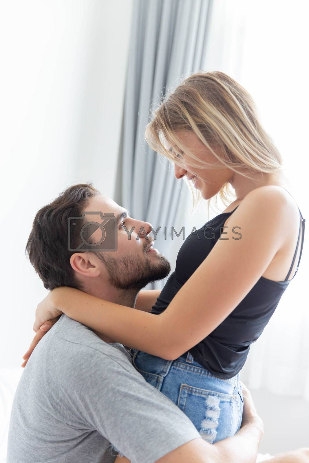 Passionate couple is hug and kiss on bed in their white bedroom