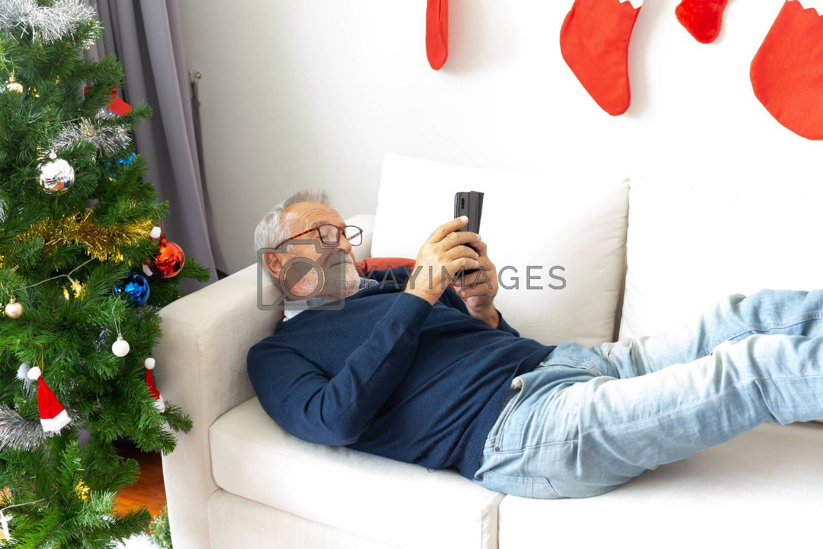 Senior retirement male relax playing his mobile phone on sofa after decorate the chritmas tree