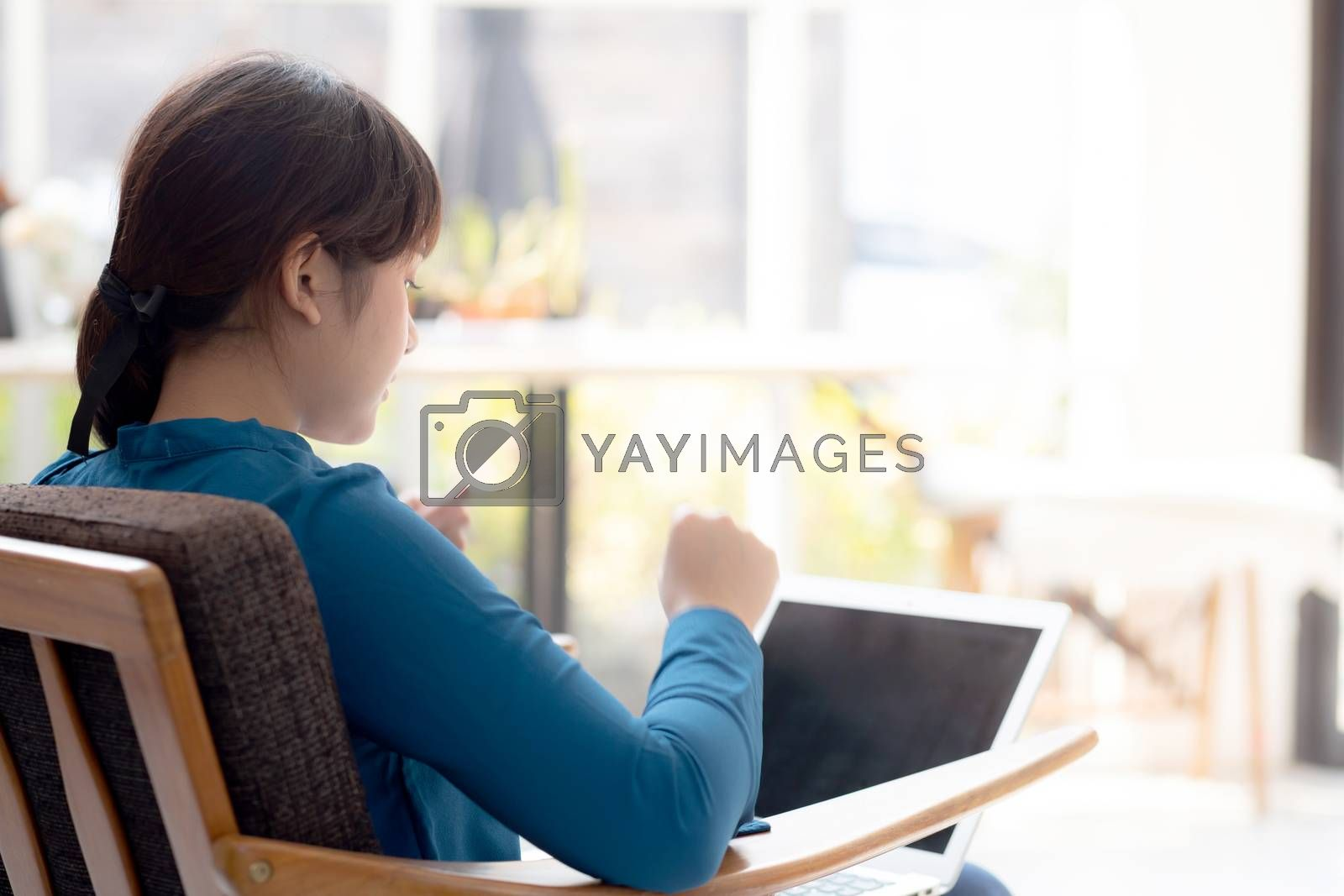 Back view beautiful of portrait happy young freelance asian woman using laptop work with success in the home, asia girl and notebook shopping online with glad, communication concept.