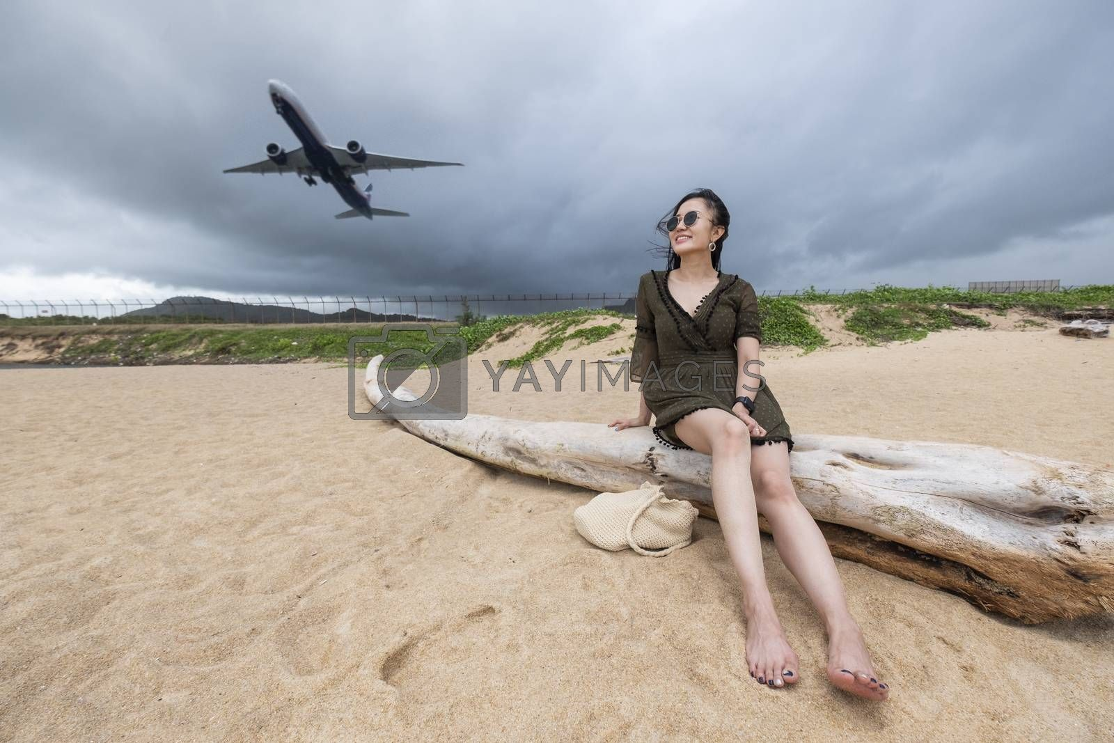 Woman tourist on the beach watching the landing planes at Island Phuket in Thailand. Impressive paradise. Hot beach Mai Khao. Amazing landscape