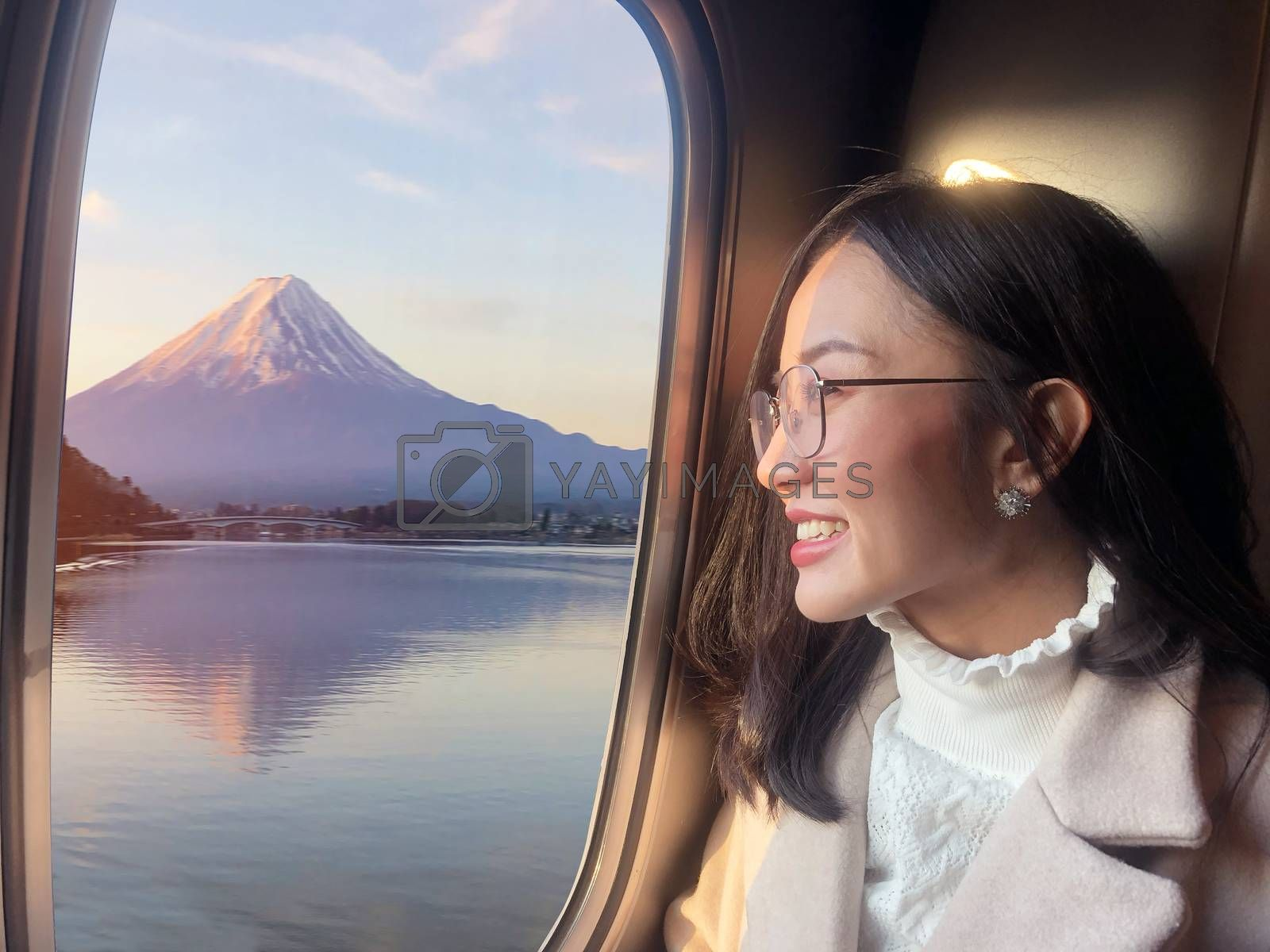 Young woman traveling by the train from sitting near the window and looking view of mountain Fuji in sunrise ,Japan