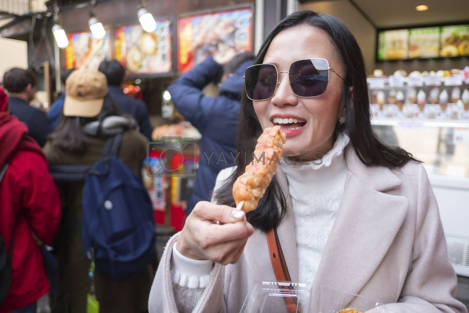 Young tourist woman eating yakitori, chicken grilled as the famous street food at bamboo forest Arashiyama in Japan
