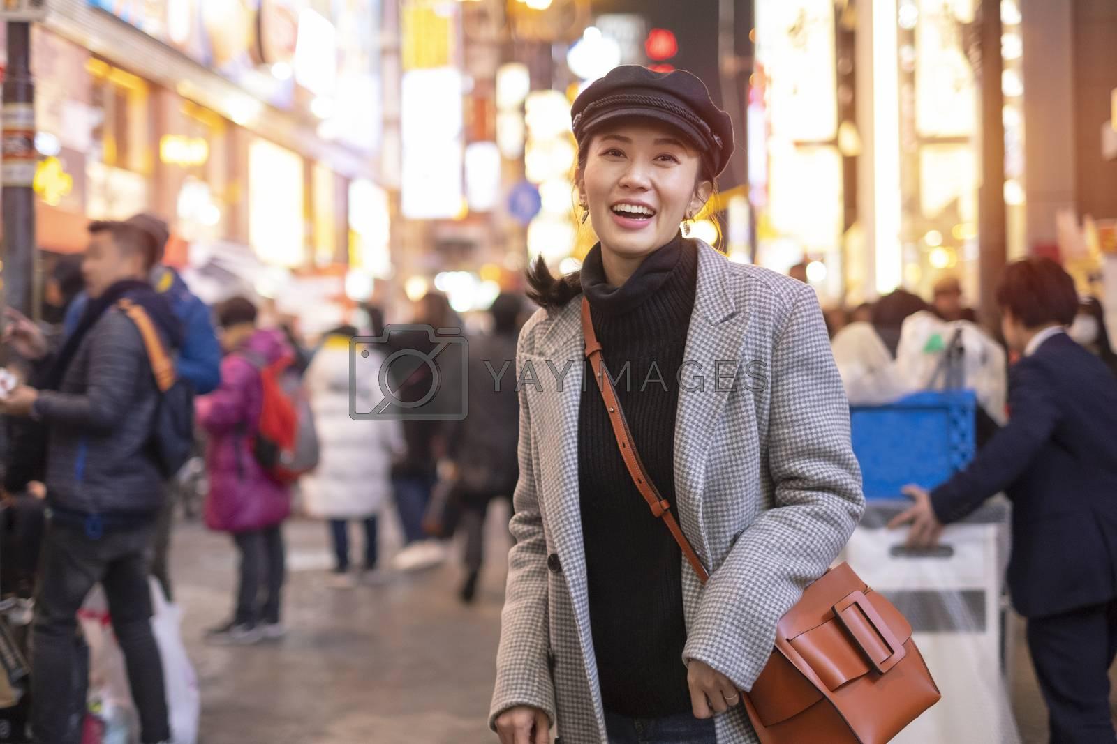Beautiful smiling woman tourists traveling in walking at street shopping center Shibuya in Tokyo, Japan.