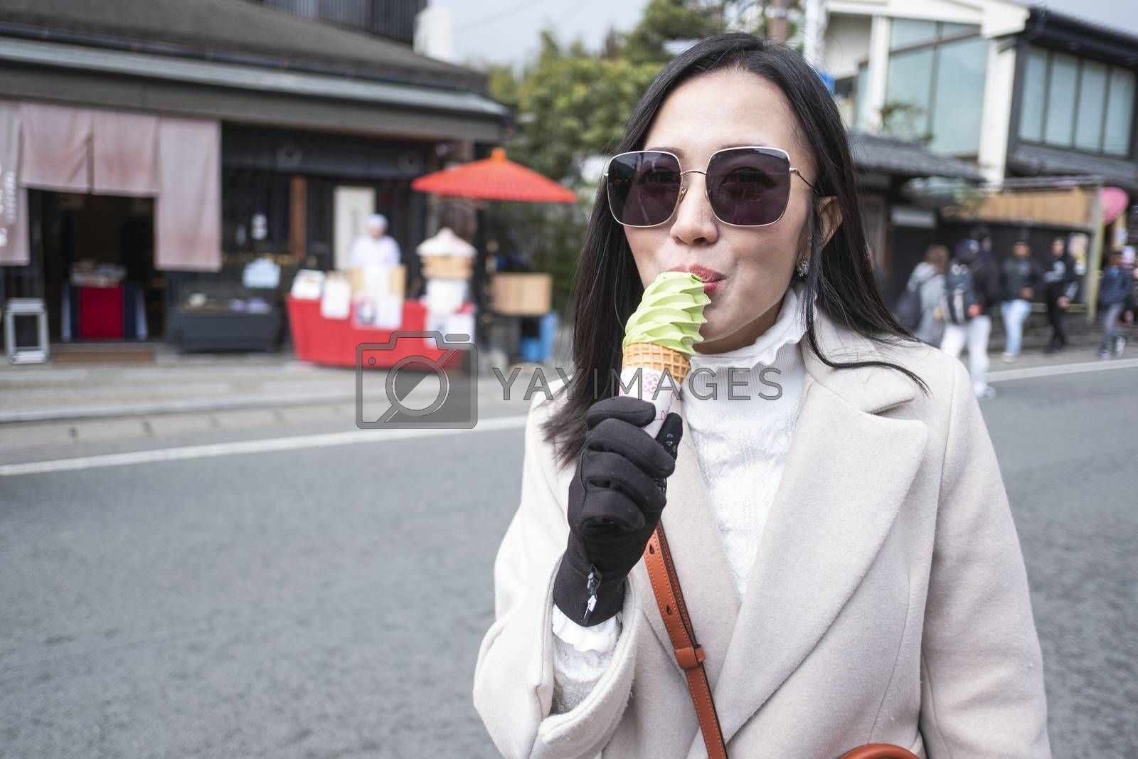 Young tourist woman eating ice cream cone street food at bamboo forest Arashiyama in Japan