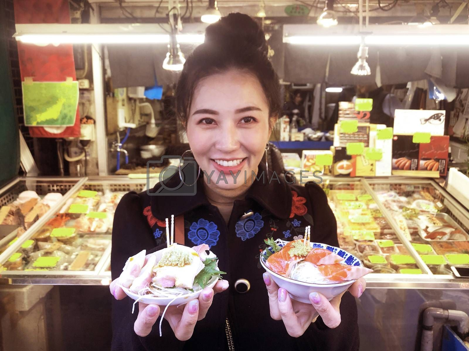 Tourist woman showing salmon sashimi most popular delicious food in street food tsukiji fish market, Japan
