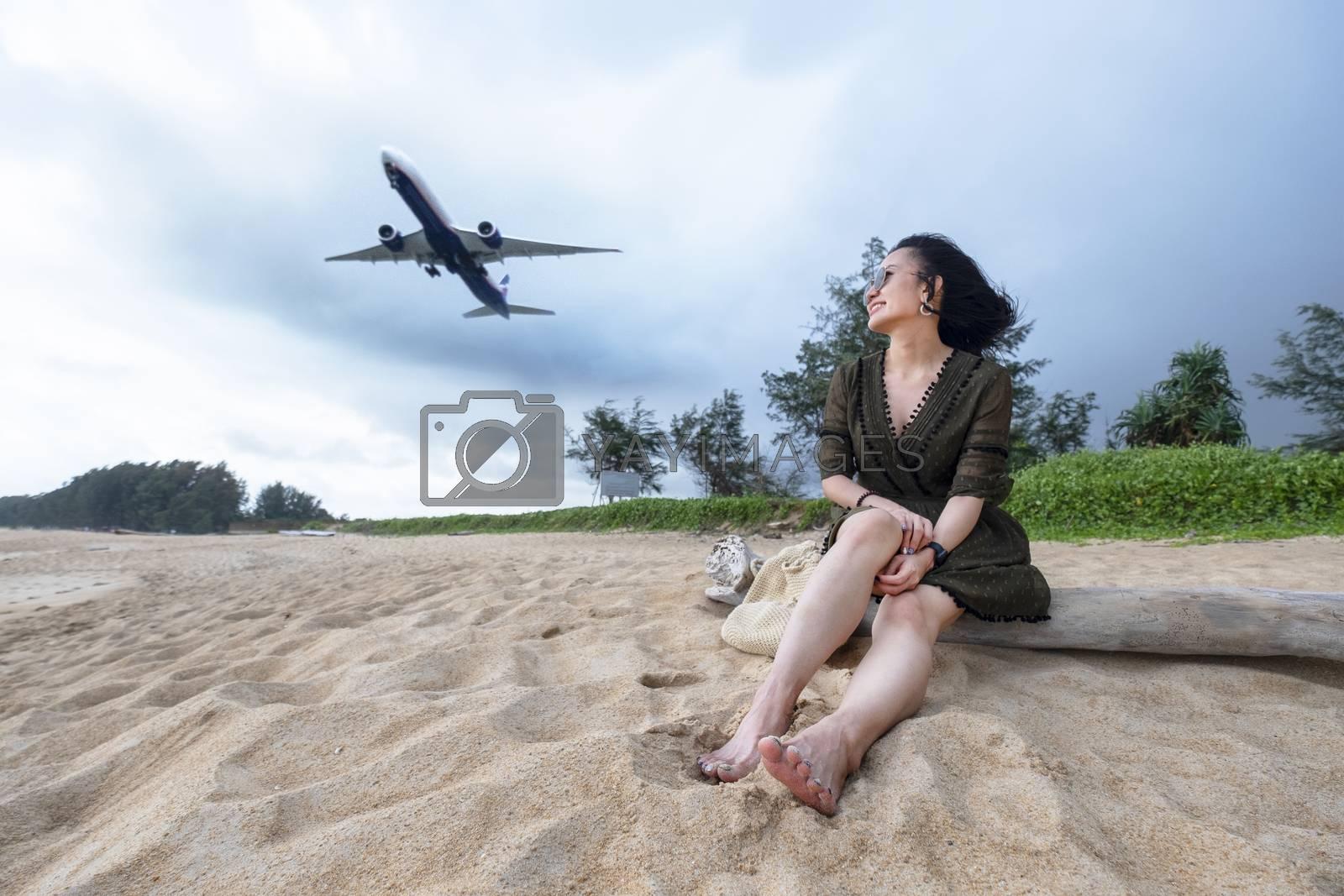 Woman tourist on the beach watching the landing planes at Island Phuket in Thailand. Impressive paradise. Hot beach Mai Khao. Amazing landscape