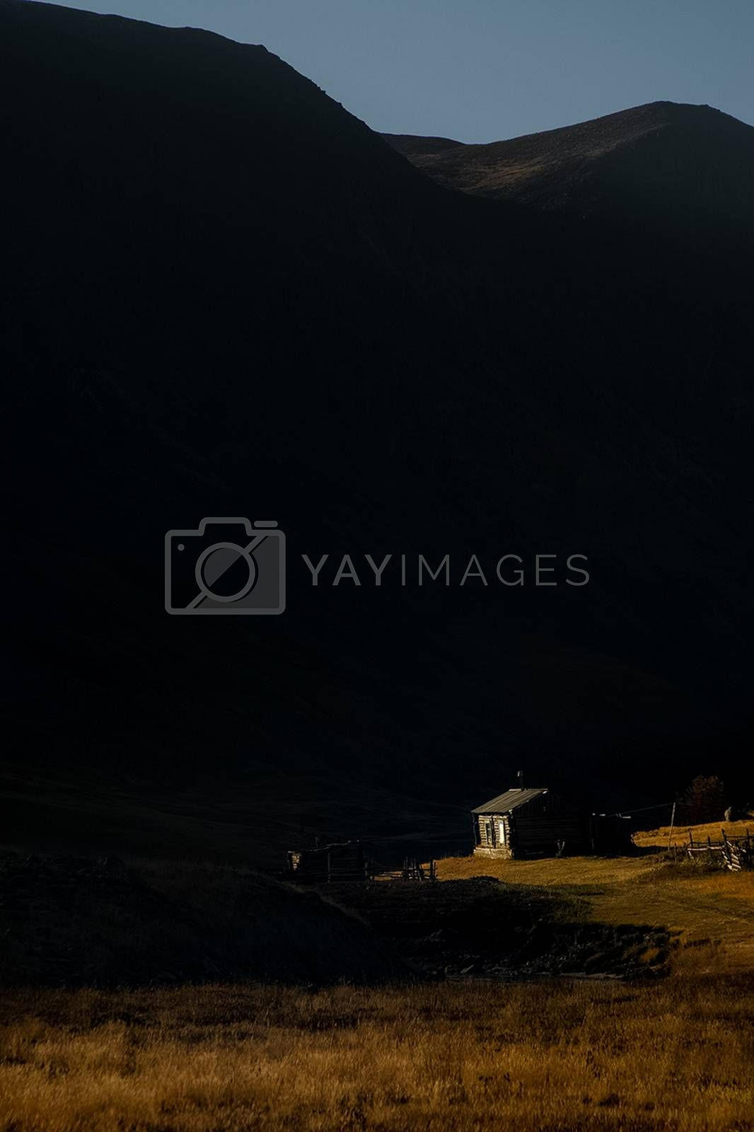 A wooden house on a hill in the altai at the foot of the high mountains.