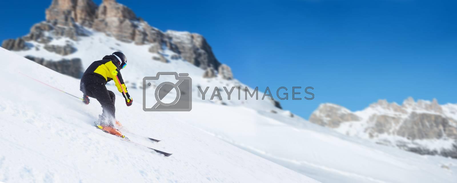Alpine mountain skier skiing downhill in high mountains Alps Dolomites region of Northern Italy ski resort piste