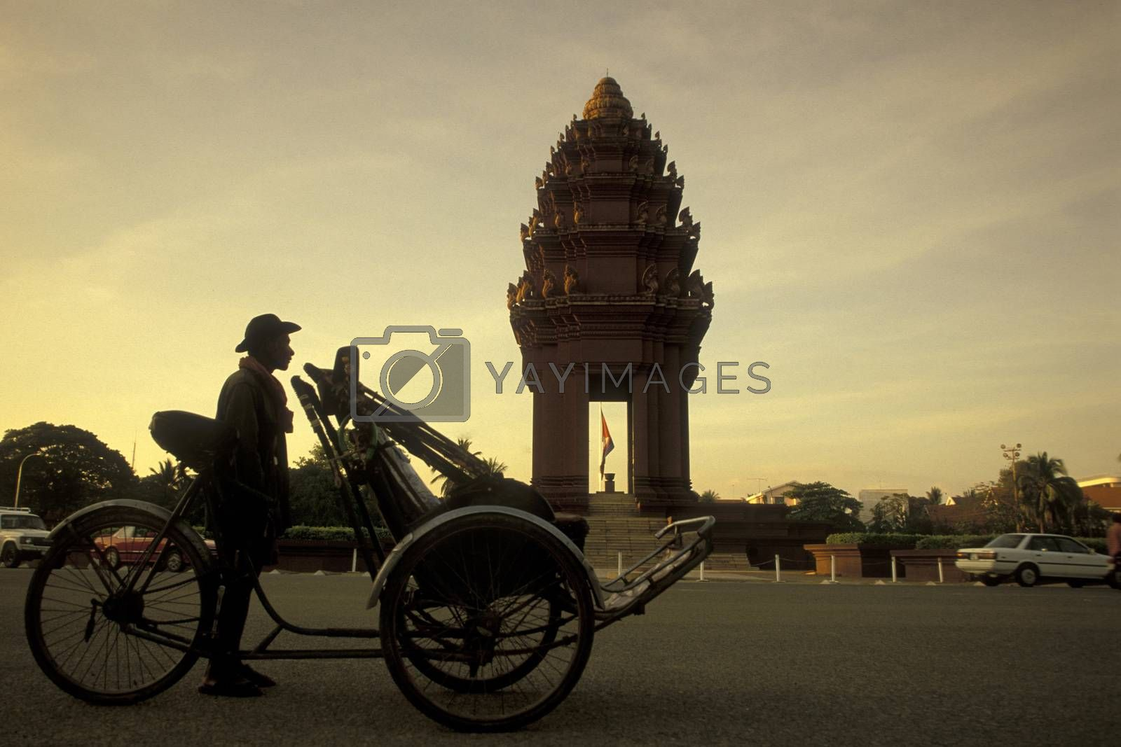 a traditional Bicycle Riksha Taxi in front of the Independence Monument at the Sihanouk Bouelvard in the city of Phnom Penh of Cambodia.  Cambodia, Phnom Penh, February, 2001