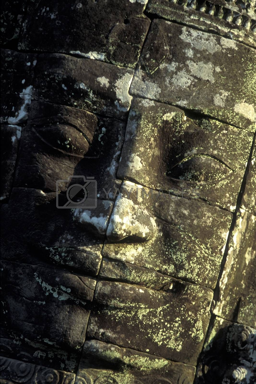 Stone face at the Bayon Temple the Tempel Ruins of Angkor Thom in the Temple City of Angkor near the City of Siem Reap in the west of Cambodia.  Cambodia, Siem Reap, February, 2001