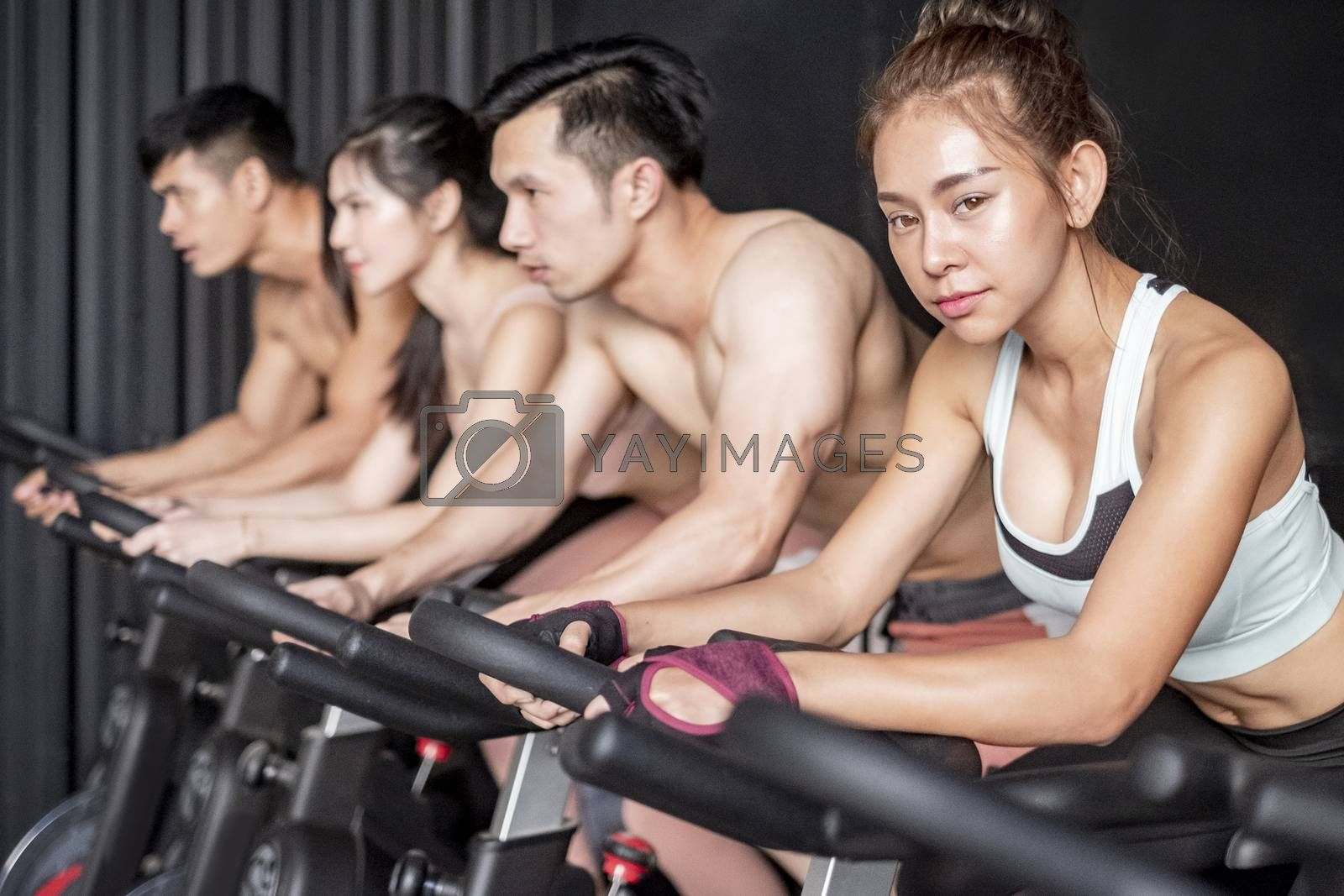 Young woman and friends on fitness bike in gym during workout